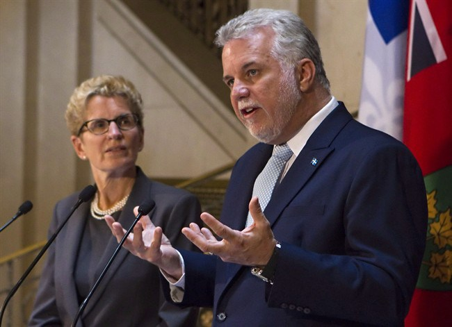 Quebec Premier Philippe Couillard addresses the Ontario legislature with Premier Kathleen Wynne